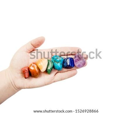 Close up view of woman healer hand showing all seven chakra color crystal stones in color order, isolated on white background. Crystal healer lifestyle concept, lot of room for text.
