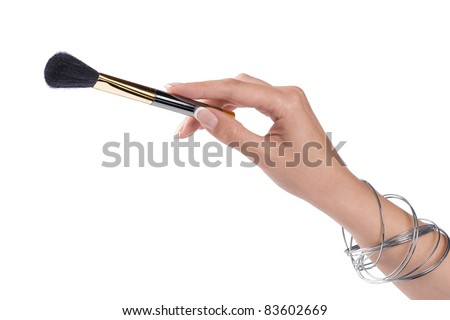 Close up view of woman's hand holding brush on color back