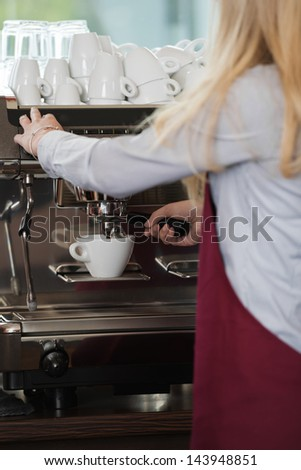close-up view of woman\'s hands brewing a cup of coffee