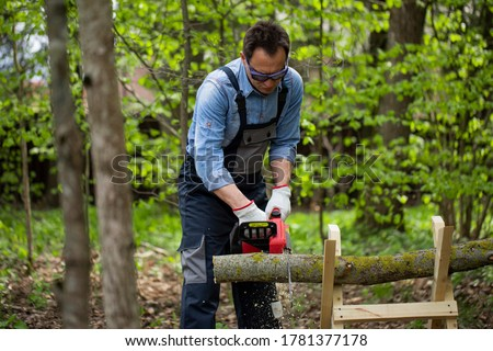 Close up view of woodcutter lumberman in working uniform sawing small tree trunk on sawhorse with electric saw chainsaw in forest on sawmill, outdoors. Wood work, handwork, wood cutting tools, timber Stock photo ©