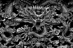 Close up view of wooden carving of a traditional ancient Chinese dragon in monochrome with intricate craftsmanship and detail as vintage background
