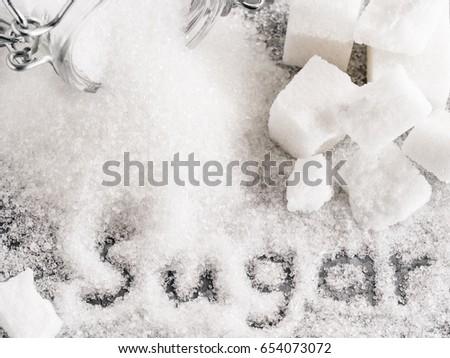Close up view of word sugar of granulated sugar. sugar cubes. Top view or flat lay. #654073072