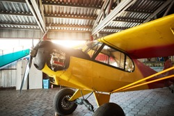 close up view of yellow single-engine propeller airplane standing in hangar building with opened motor cabinet, waiting for maintenance and service works.