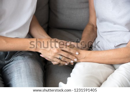 Close up view of young woman daughter holding old mother female hands as concept of different older and younger generations support, giving love and care to senior people, helping elderly parents
