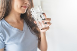 Close up view of young woman drinking pure mineral water in a glass.