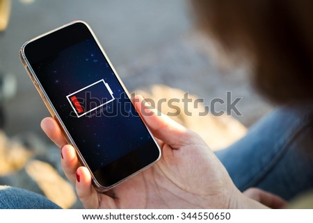 close-up view of young woman holding a smartphone with low battery on screen. All screen graphics are made up.