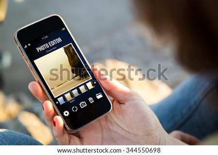 close-up view of young woman holding a smartphone with photo editor app on screen. All screen graphics are made up.