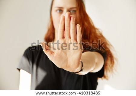 Close up view of young woman making stop gesture with her hand. Cropped isolated portrait of redhead female in cap and black T-shirt standing against white background.