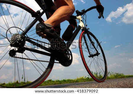 Close-up view on a cyclist on the road. Detail of a cyclist on bicycle. Road biker riding a bike on the road view from below. Cyclist rides on a background of blue summer sky.
