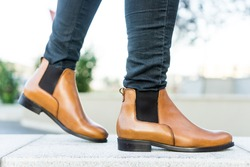 Close up view on a girl in dark jeans and brown chelsea boots