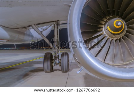 Close-up view on Airbus A320-232 aircraft's IAE V2500 engine, fuselage and left main landing gear at night. Tbilisi International Airport, Tbilisi, Georgia Stock photo ©