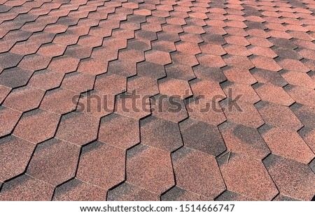 Close up view on Asphalt Roofing Red Shingles Background. Roof Bitumen Shingles - Roofing Construction, Roofing Repair. Red Shingles on the Roof of the House. Background of Red Shingles