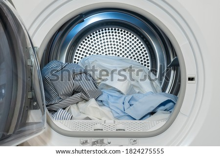 Close up view on clothes dryer with washed and dried shirts in and door open.