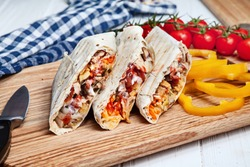 Close up view on delicious cuted shaurma or shawerma on board on white background. Shaurma with spices, cherry tomato and bell pepper. Arab or Eastern cuisine food with copy space. Fastfood kebab
