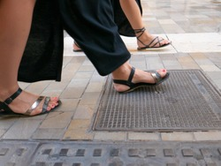 Close up view on female legs with open toes shoes walking on the street.