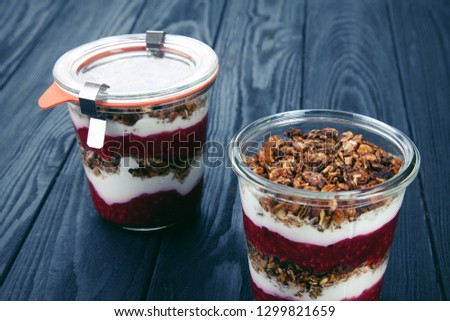 Close up view on healthy Homemade Granola Parfait in jar with jam. Quick Healthy Breakfast Greek Yogurt Parfait. Selective focus. free copy space. Menu photo. Vegetarian food lifestyle #1299821659