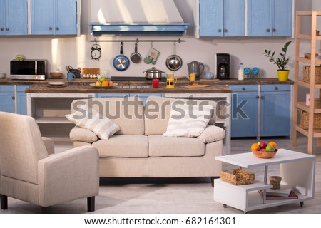 Close up view on kitchen studio. Living room with small sofa, chair and coffe table with kitchen on background.