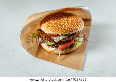 Close up view on meat burger wrapped in brown paper  Stock photo ©