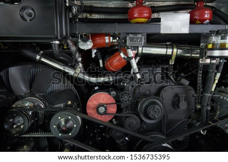 Close up view on new bus engine components, parts and elements. Motor, pulleys with belt, gear, pneumatice hoses, fuel tubes. Commercial transport engine compartment #1536735395