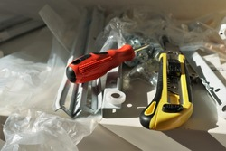 Close up view on paper cutter with yellow black plastic handle and snap off utility blade and red screwdriver together with dismantled part of drawer lying on transparent plastic.