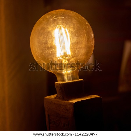 Close up view on round vintage light bulb in dark room #1142220497