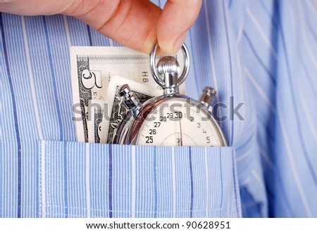 Close up view on stopwatch and banknotes into the pocket of shirt