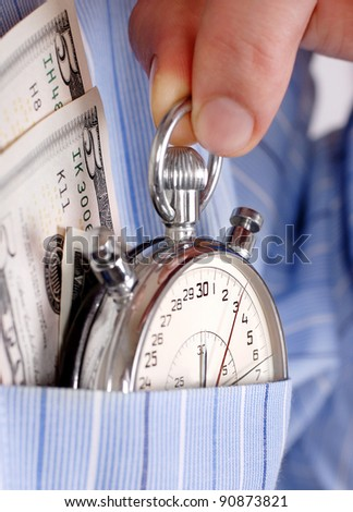 Close up view on stopwatch with banknotes into the pocket of  man shirt