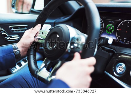 Photo of Close up view on the businessman in blue suit  who drives the luxury car