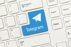 Close-up view on white conceptual keyboard - Telegram (blue key with logotype)