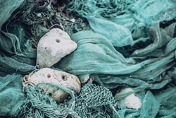 Close up view pile of green nylon multi colorful bright fish nets with pieces of white corals and old ropes in fishing village. Still life background pattern. Hobby fishing concept. Copy space