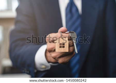 Close up view realtor broker holding home keychain in his hand.