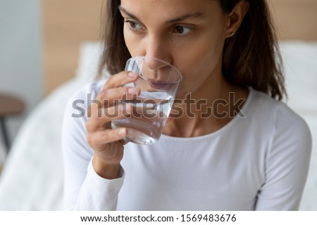 Close up view 30s thirsty woman holding glass drinking still or mineral water preventing organism dehydration, maintain normal aqua balance of body, skin and health care, concept of healthy lifestyle
