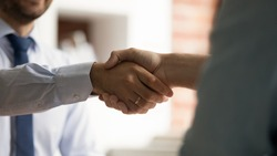 Close up view two businessmen shaking hands after successful formal negotiations. Male HR manager handshake hire candidate at job interview. Mutual respect, business etiquette, make agreement concept