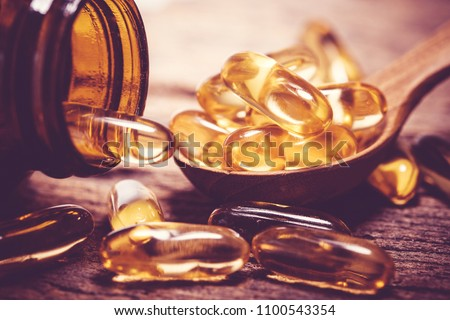 Close up vitamin D and Omega 3 fish oil capsules supplement on wooden plate for good brain , heart and health eating benefit