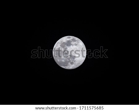 Close up vivid photograph of a full moon worm moon or sap moon supermoon centered on a black night sky background showing craters and detailed texture of the moon surface.
