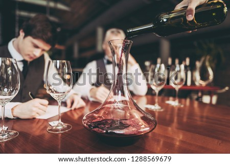 Close up. Waiter's hand pouring red wine from bottle into decanter in restaurant. Wine tasting. Experienced sommelier pours wine into glass from decanter