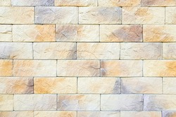 Close-up wall background with brick stone texture in warm pastel colors. Pattern for design and decoration. Mobile Photo. New facade of building made of sandstone blocks