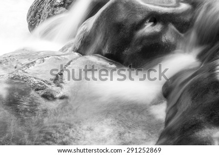 close up water fall at national park of thailand. smooth water line falling to the stream on black and white tone