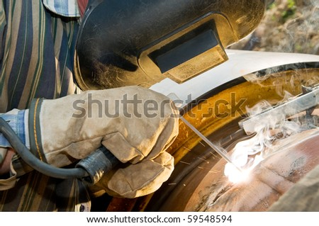 close-up welder works with electrode in protective helmet and glows