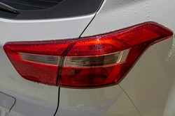 Close-up wet clean and good condition white car red tail light with water drops. Clear glass turn signal and reversing lights lit by sunlight with copy space. Exterior details