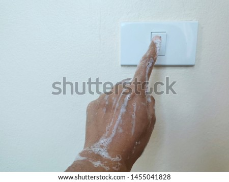 Close up wet hand woman is turn on or turn off on the light switch. Do not use electricity while wet hands concept.  Safety concept. #1455041828