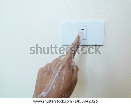 Close up wet hand woman is turn on or turn off on the light switch. Do not use electricity while wet hands concept.  Safety concept. #1455042326