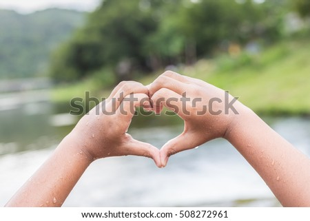 Close up wet hands with heart sign at the river in Thailand #508272961