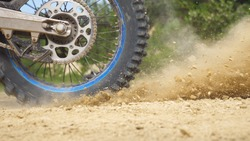 Close up wheel of powerful off-road motorcycle spinning and kicking up dry ground. Professional motocross rider starting race or training. Active lifestyle concept. Side view Slow motion.