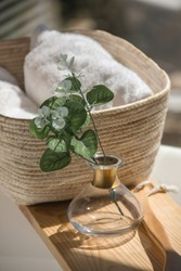 close-up white bath towels in a wicker basket next to accessories on a wooden shelf in the white bathroom at morning