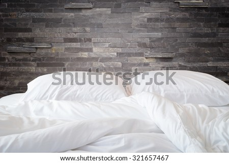 Close up white bedding sheets and pillow on natural stone wall room background, Messy bed concept