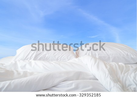 Close up white bedding sheets and pillow on view of sky background