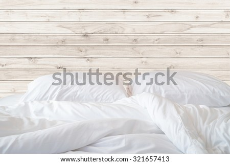 Close up white bedding sheets and pillow on wooden wall room background, Messy bed concept