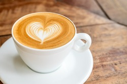Close up white coffee cup with heart shape latte art on wood table at cafe