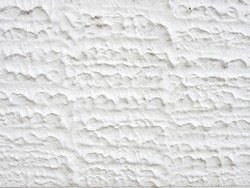 close-up white concrete wall texture background, cement walls are decorated with plastering techniques to have rough surface like cement dripping for decoration exterior facade building wall